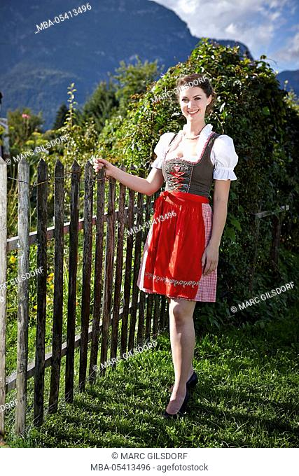 Young woman in dirndl, standing at fence