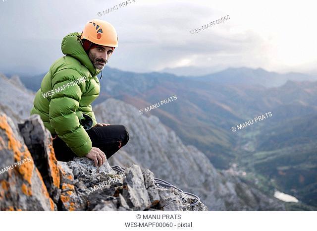 Spain, Picos de Europa, climber resting on rock