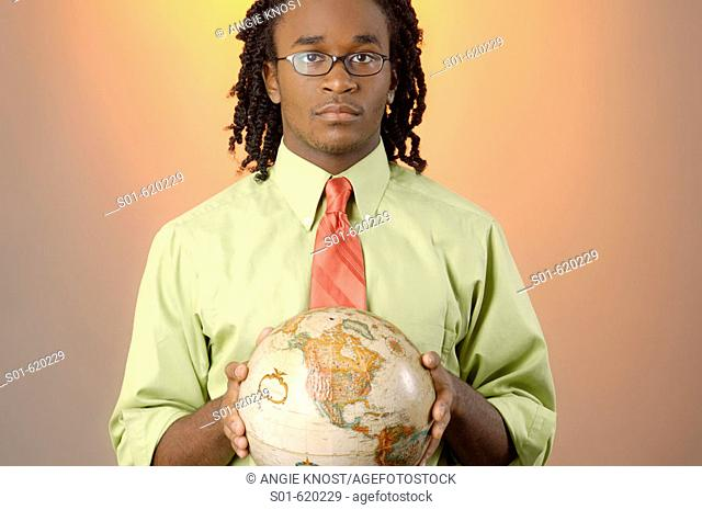 This stock photo shows a young business man of African descent, age 25-30, holding the globe in his hands.  North American side of globe is facing the viewer