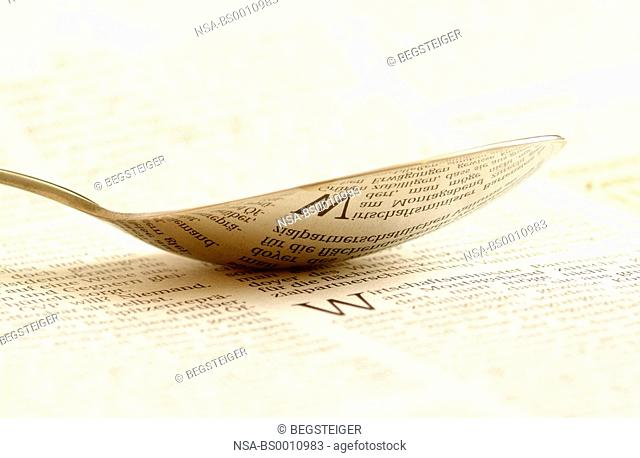text reflected in a spoon