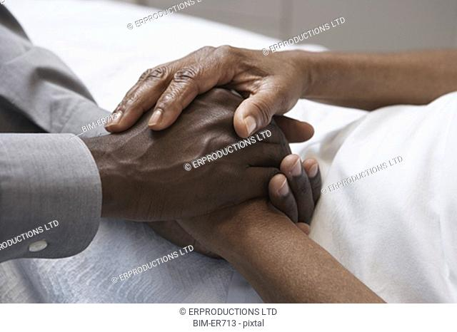 Close up of African man holding hands in hospital