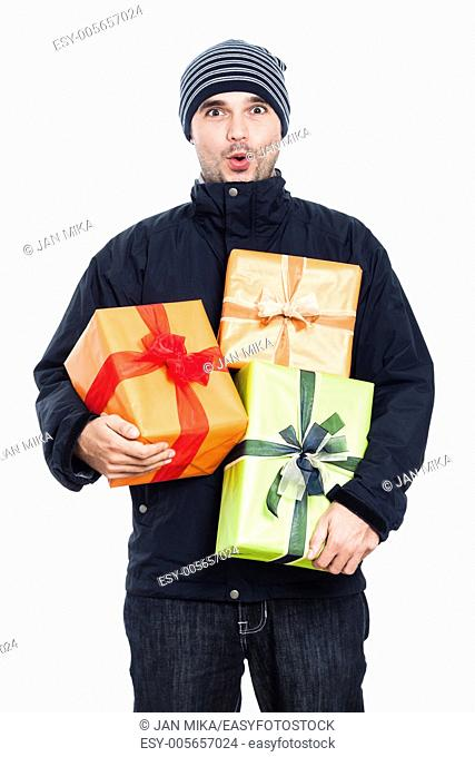 Surprised man in winter jacket holding presents, isolated on white background