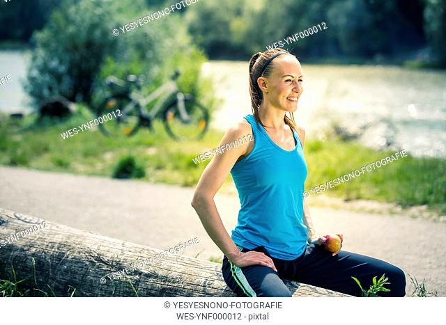 Smiling young woman sitting on log holding an apple