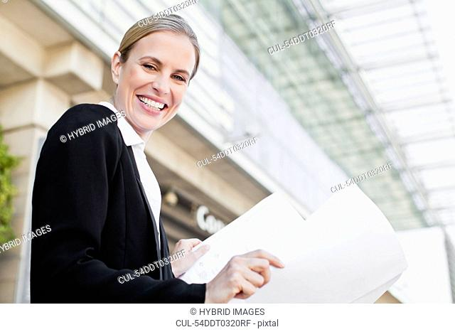 Businesswoman reading blueprints