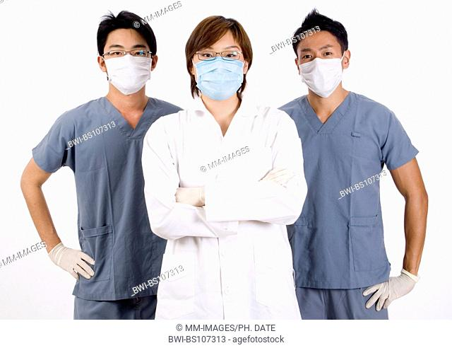 three Asian doctors in scrubs and with face masks, a young woman is flanked by two men