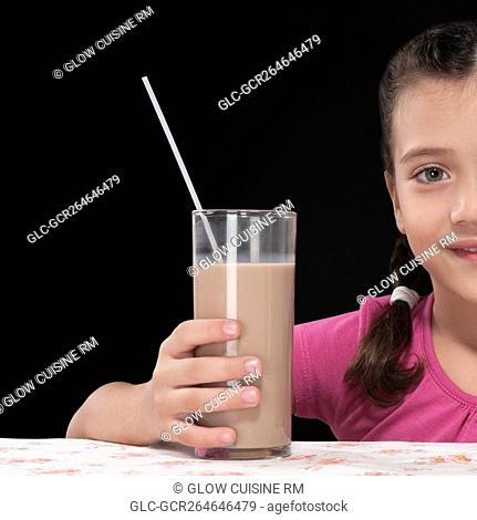 Close-up of a girl holding a glass of chocolate milkshake