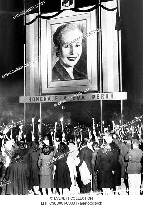 Honor Eva Peron. Argentines mourning the death of Eva Peron beneath a huge portrait of the deceased wife of their nation's President, Juan Peron