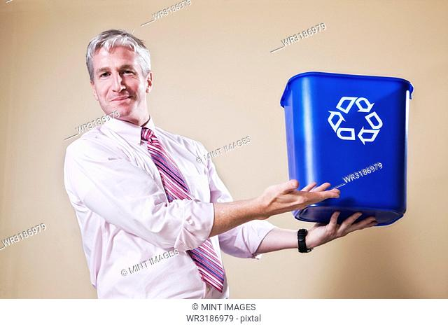 Caucasian man in shirt and tie holding a recycle waste bin
