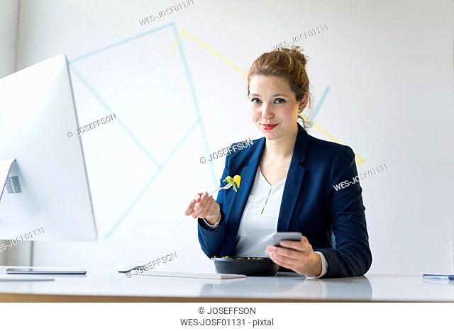 Businesswoman eating lunch in office