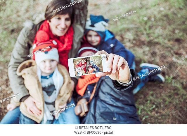 Family taking a selfie with smartphone in forest