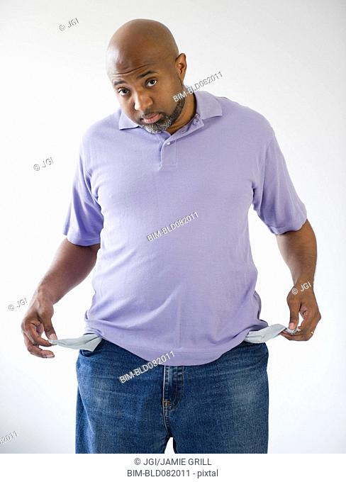 Sad African American holding out empty pockets