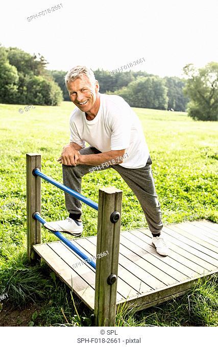 MODEL RELEASED. Senior man leaning on gate, smiling