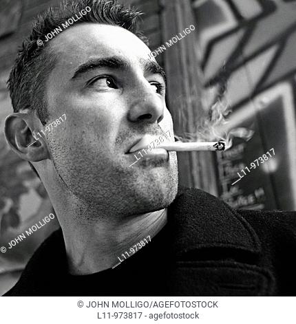 Close-up of man in alley, smoking a cigarette