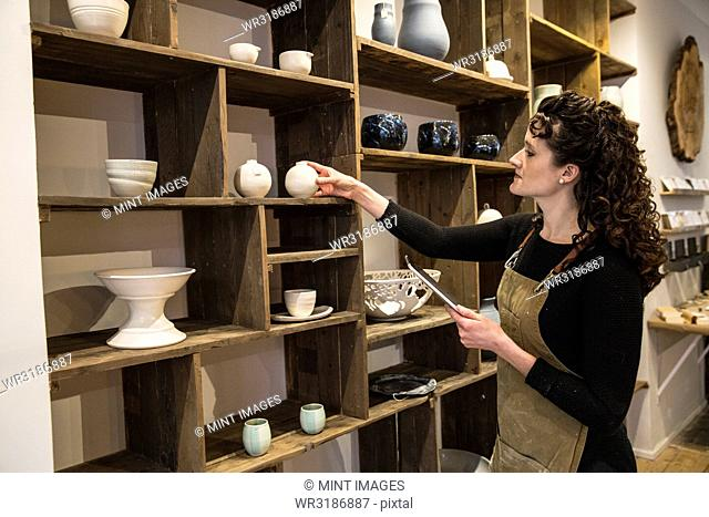 Woman with curly brown hair wearing apron standing in her pottery shop, arranging ceramic items on shelves, holding digital tablet