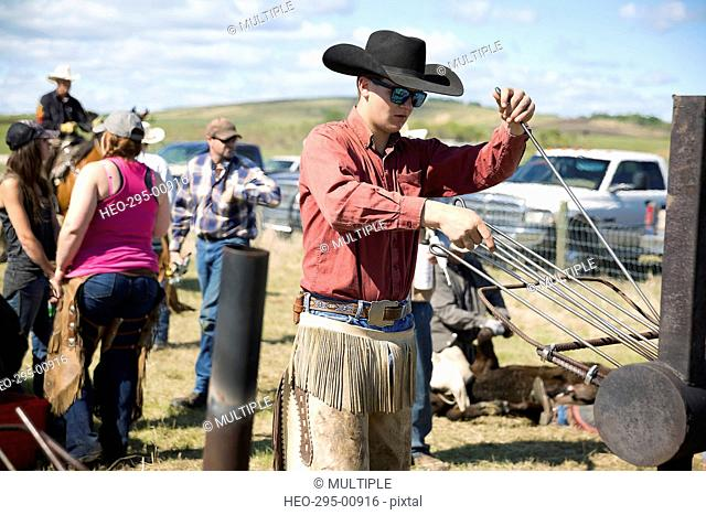 Cattle rancher preparing branding iron at fire
