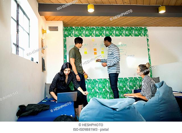 Young businessmen and women using laptop and whiteboard in creative meeting room