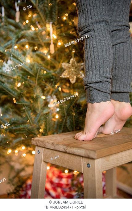 Feet of Caucasian girl standing on stool decorating Christmas tree