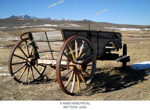Abandoned old horse-drawn carriages on farmland. Along Cowboy Trail (Hwy 22) near Longview. Rocky Mountains in background