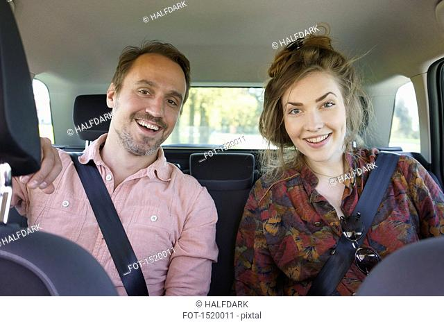 Portrait of happy couple sitting in car