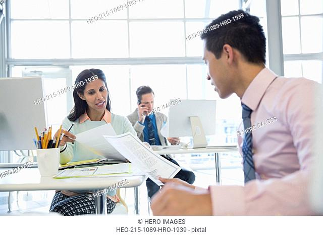 Business people with paperwork talking in office