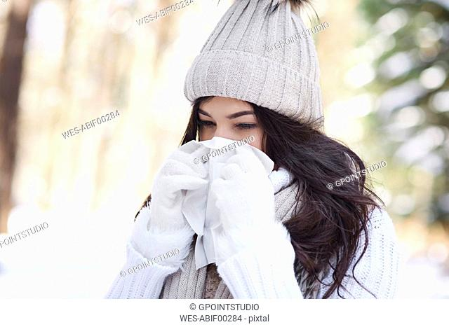 Young woman blowing nose in winter