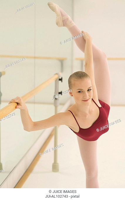 A ballet dancer stretching her back leg whist holding on to the barre