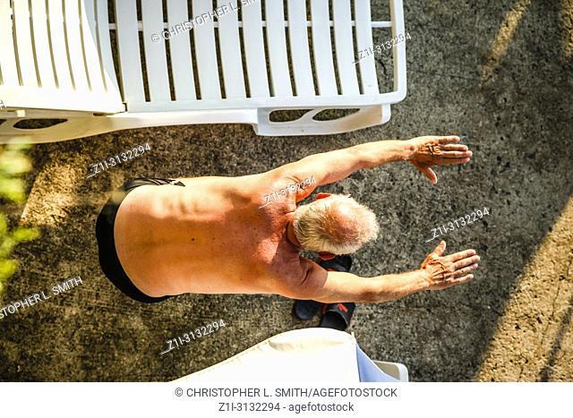 Senior male undertaking stretching exercises on the beach at Opatija in Croatia
