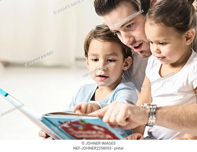 Male preschool read story in preschool