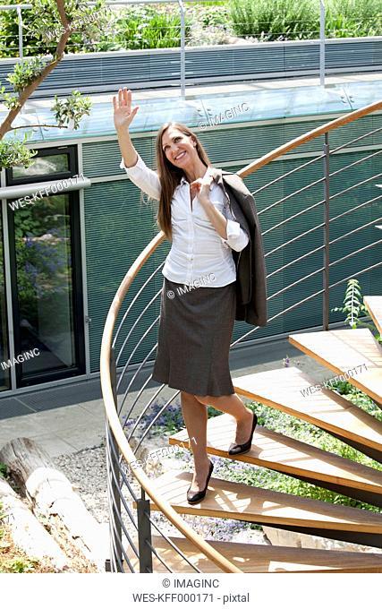 Businesswoman on spiral staircase waving her hand