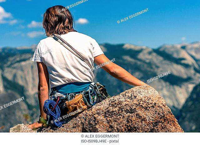 Rear view of rock climber on Higher Cathedral Spire looking away at view, Yosemite Valley, California, United States