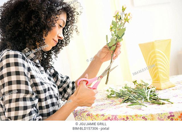 Mixed race woman cutting flower stems at table
