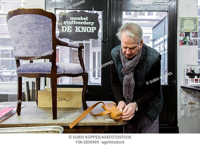 Tilburg, Netherlands. The 75 year old upholsterer Boy packing his latest things before partially retiring and moving his business homebound