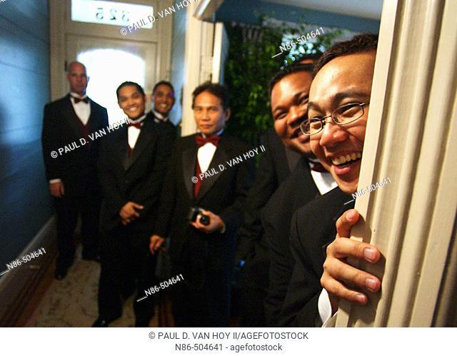 Groomsmen peeking around door frame