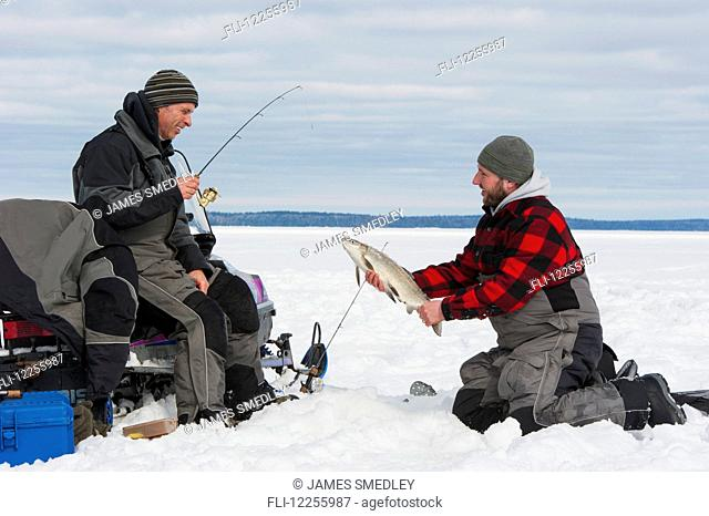 Two ice fishermen, one holding a large whitefish; Ontario, Canada