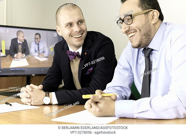 laughing business men at conference, lawyers consulting at online live stream, in office, in Cottbus, Brandenburg, Germany