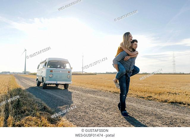 Young man carrying girlfriend piggyback on dirt track at camper van in rural landscape
