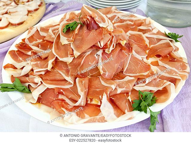 Plate with slices of ham on buffet table