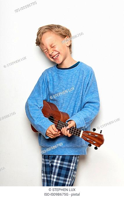 Boy playing ukulele, eyes closed, laughing