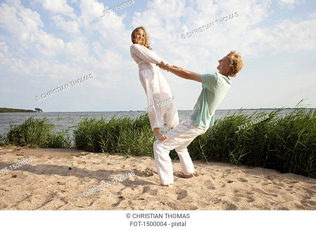Woman balancing on friend's knee at beach against sky