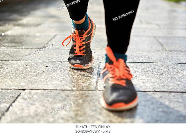 Legs of woman wearing running shoes on pavement
