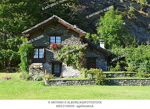 Alpine building made of rocks and decorated with plants and flowers. antigorio valley. piemonte. italy. europe