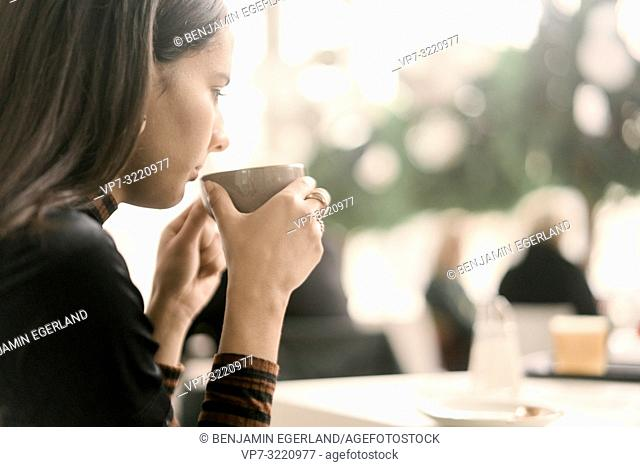 woman drinking coffee at coffee shop, in Munich, Germany