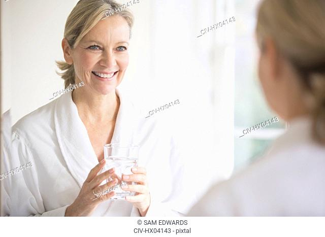 Smiling, confident mature woman in bathrobe drinking water at bathroom mirror