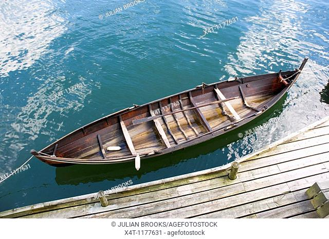 A traditionally build wooden Norwegian rowing boat from above, tied to the quayside