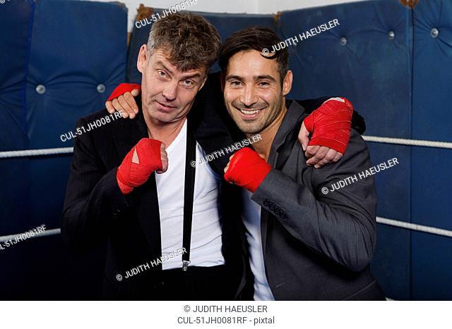 Smiling boxers hugging in ring