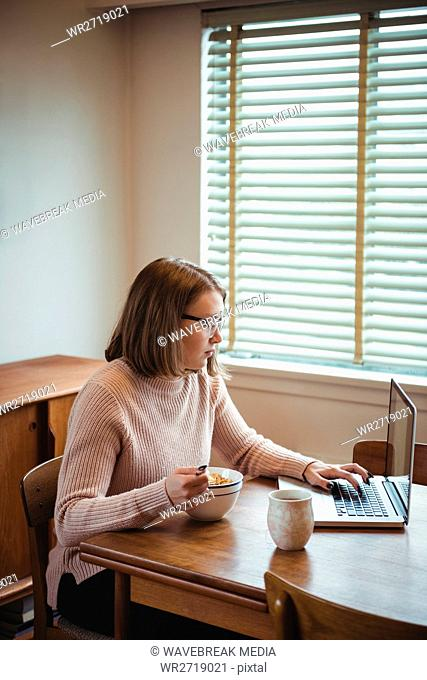 Woman using laptop while having breakfast in living room