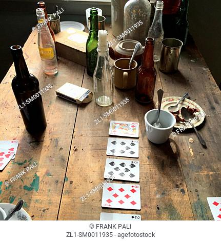 Old dirty table with playing cards and bottles