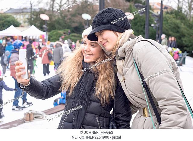 Sisters taking selfie on ice rink