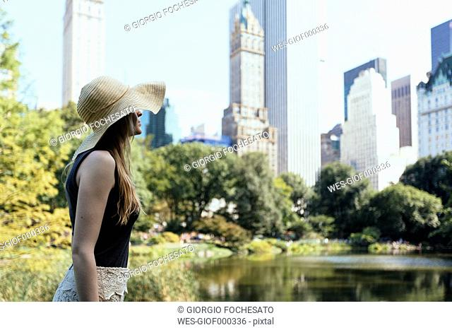 USA, New York City, young woman wearing summer hat in Central Park