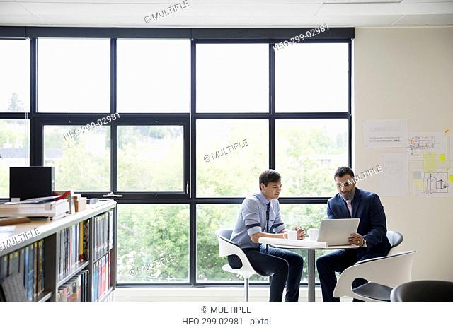 Architects with digital tablet meeting at table in office window